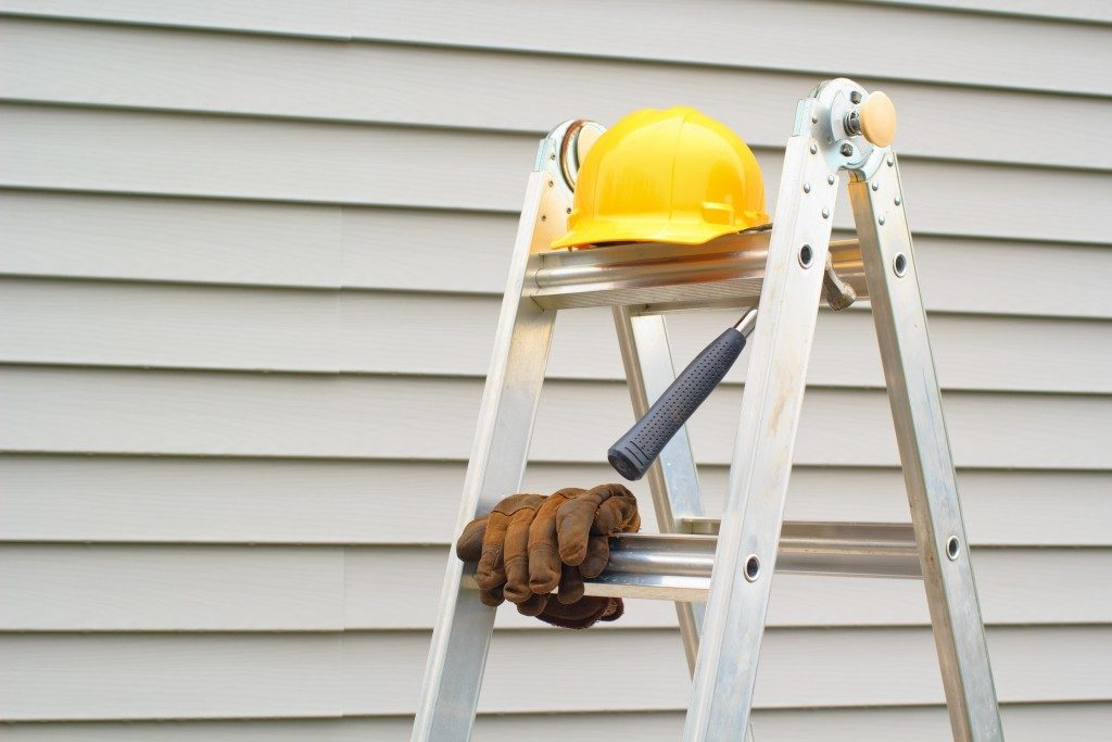 ladder and safety gear beside house's exterior