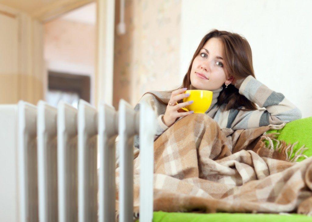 a woman beside her heater