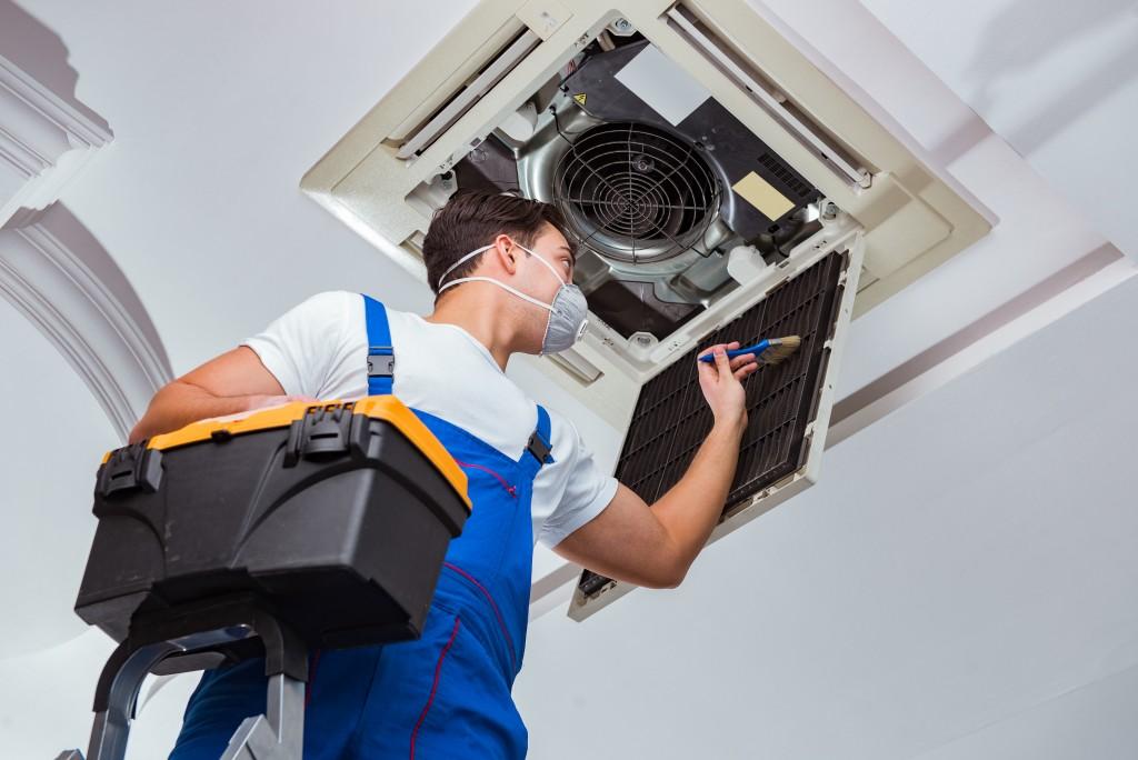 man repairing the AC unit