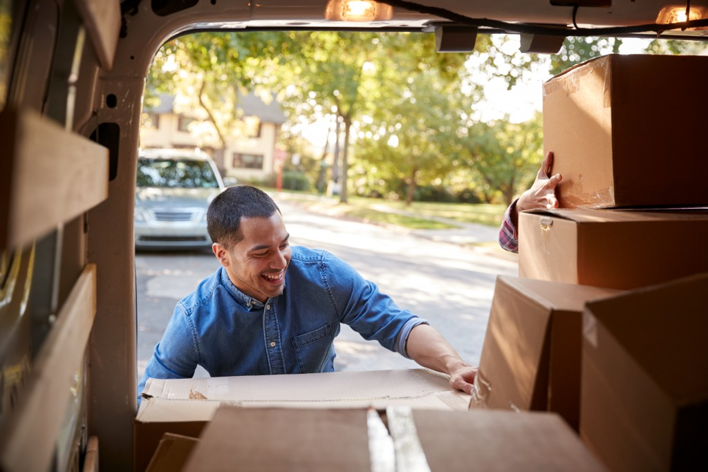 Man bringing out boxes from moving van