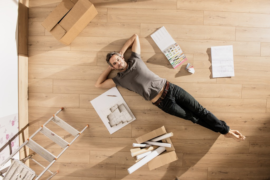 man laying on the floor planning renovation