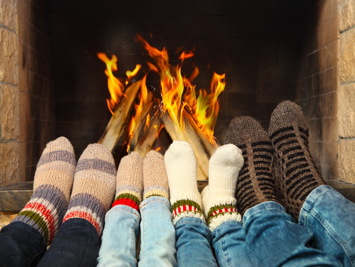Feets wearing socks by the fireplace