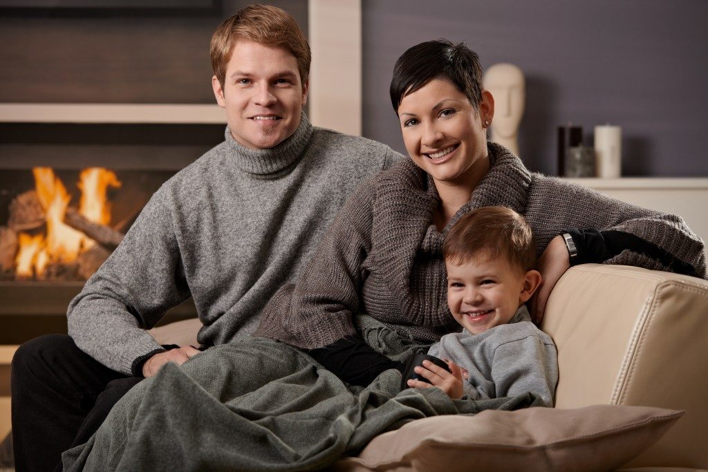 Family keeping warm by the fireplace