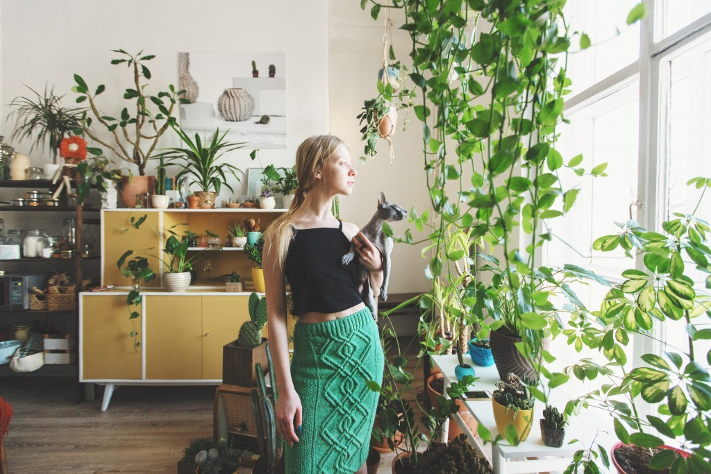 woman in her apartment surrounded by plants